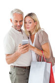 Happy couple holding shopping bags and smartphone — Stock Photo