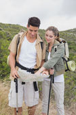 Couple looking at map on mountain terrain — Stock Photo