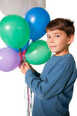 Little boy holding bunch of balloons — Stock Photo
