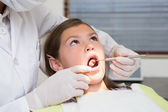 Pediatric dentist examining a little girls teeth — Foto Stock
