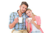 Attractive young couple sitting holding mugs — Foto Stock