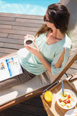 Woman drinking tea by pool with breakfast on table — Stock Photo