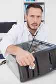 Computer engineer listening to console with stethoscope — Stockfoto