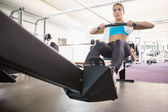 Woman working on fitness machine at gym — Stok fotoğraf