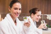 Smiling women in bathrobes drinking water — Stock Photo