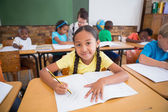 Pupils writing at desk in classroom — Stock Photo