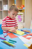 Little boy folding paper shapes — Stock Photo