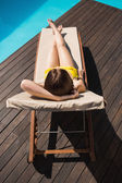 Beautiful woman in bikini relaxing by pool — Zdjęcie stockowe