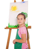 Little girl painting on easel — Stock Photo