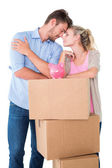 Attractive young couple leaning on boxes with piggy bank — Stock Photo
