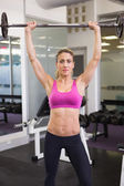 Fit young woman lifting barbell in gym — ストック写真