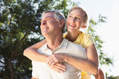 Happy senior man giving his partner a piggy back — Stock Photo