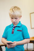 Pupil using smartphone in classroom — Stockfoto