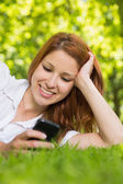 Redhead lying on the grass sending a text — Stock Photo
