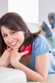 Pretty brunette wearing earphones around neck on the couch — Stock Photo