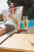 Woman reading book by pool with champagne in foreground — Stock fotografie