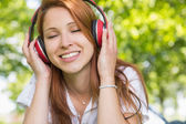 Redhead listening to music in the park — Foto de Stock