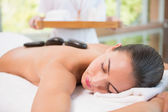 Beautiful woman receiving stone massage at health farm — Foto de Stock