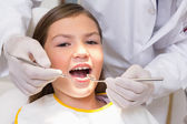 Pediatric dentist examining a patients teeth — 图库照片