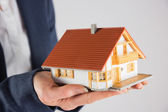 Businesswoman holding miniature model house — Stock Photo