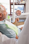 Patient admiring new smile in the mirror — Stock Photo