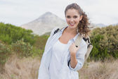 Smiling woman standing on countryside landscape — Stock Photo