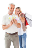 Happy couple holding shopping bags and cash — Stock Photo