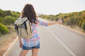 Woman hitchhiking on countryside road — Stock Photo