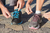 Couple tying their laces of running shoes — Stock Photo