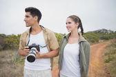 Hiking couple holding camera on mountain terrain — Stock Photo