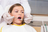 Pediatric dentist examining a patients teeth — ストック写真