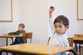 ученик, поднимать руку на своем столе — Стоковое фото