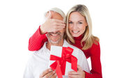 Smiling woman covering partners eyes and holding gift — Foto Stock