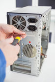 Computer engineer working on broken console with screwdriver — Stockfoto