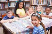 Cute pupils in library — Stock Photo