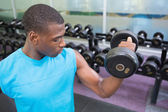 Young man exercising with dumbbell in gym — Foto Stock