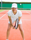 Pretty tennis player smiling at camera — Stock Photo