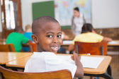 Pupil smiling at his desk in classroom — Stock Photo