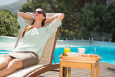 Woman relaxing by pool with breakfast on table — Stock Photo
