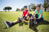 Fit mature couple tying up their roller blades on the grass — Stock Photo