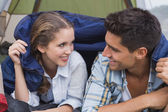 Happy young couple lying in tent — Stock Photo