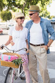 Happy mature couple going for a bike ride in the city — Stock Photo