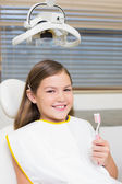 Girl holding toothbrush in dentists chair — Stock Photo