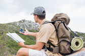Hiking man with map on mountain terrain — Stock Photo