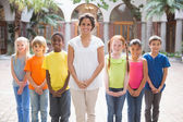 Teacher standing with pupils in courtyard — Stockfoto