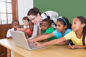 Teacher and pupils looking at laptop — Stock Photo
