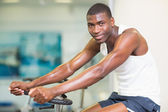 Portrait of man working out on exercise bike at gym — Stock Photo