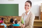 Pretty teacher at back of classroom — 图库照片