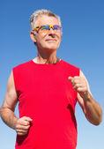 Active senior man jogging on the pier — Stockfoto