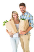 Attractive couple holding their grocery bags — Stock Photo